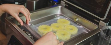 Pineapple slices in a bag, with hands putting them inside a chamber vacuum sealer.