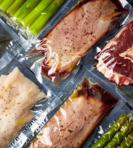 Top view of a variety of foods inside vacuum-sealed bags.