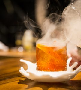 Side view of a cocktail glass being infused with smoke.
