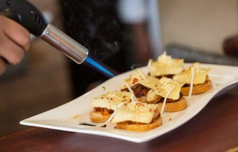 Close up image of a plate with hors d'oeuvre being finished with a kitchen torch that is heating the food.