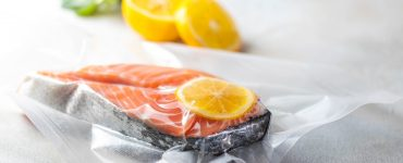 Side view of a vacuum-sealed bag with a cut of fish and lemon.
