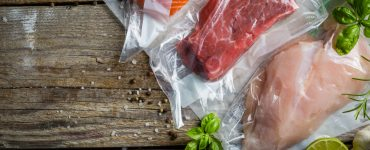 Top view of pieces of steak, chicken, and fish in vacuum sealed bags.