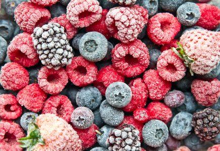 Top view close zoom of several frozen raspberries, strawberries, blueberries, and blackberries.