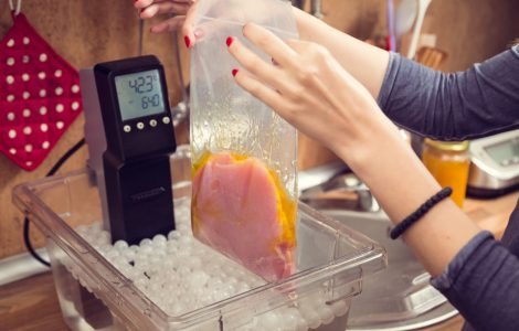 Woman putting vacuum-sealed bag of food into water container with sous vide machine.