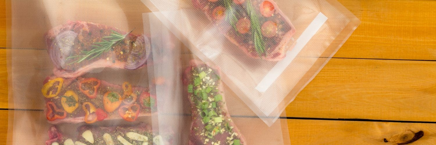 Top view of three vacuum-sealed bags with pieces of steak and herbs on top of a wooden table.