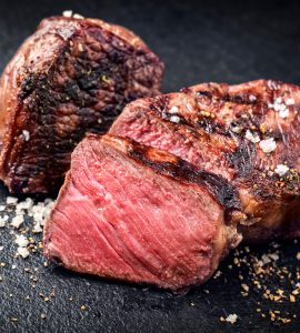 Close-up shot of pink slices of steak on a dark background.