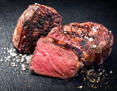 Close-up shot of pink slices of steak on a dark background.
