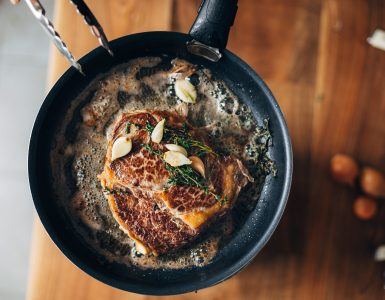 Overhead shot of a pan with a steak cooking in butter, thyme, and garlic.