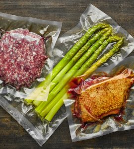 Top view of three vacuum-sealed bags, containing respectivelly ground beef, asparagus, and chicken.