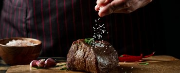 Close up shot of a steak and a chef's hand salting it.