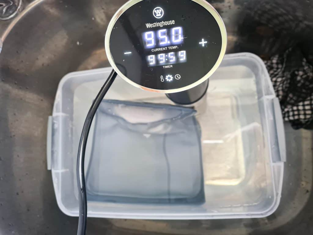 Top view of container with water, a immersion sous vide machine set at 95 degrees for 100 hours, and the Stasher bag.