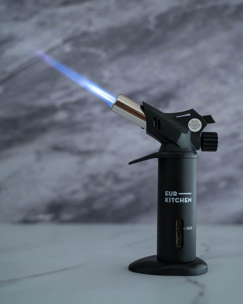 Side view of the EurKitchen Torch turned on with a long blue flame coming out of it.