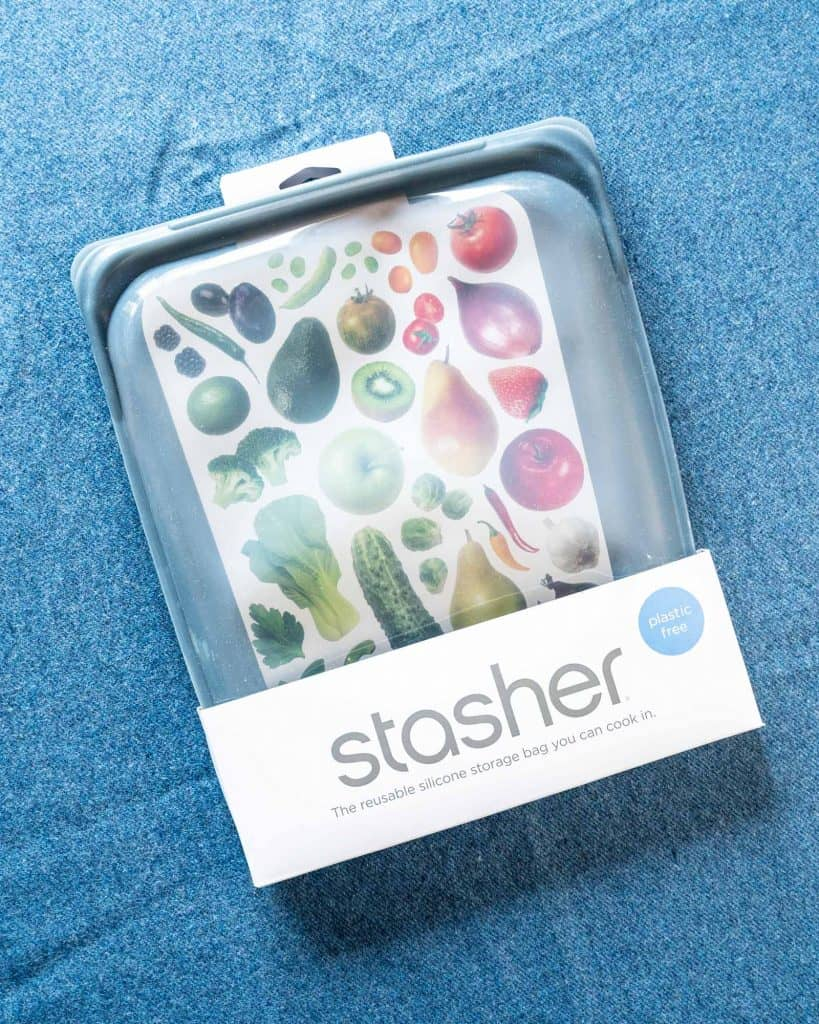 Top view of Stasher bag still in its package over a blue sheet.
