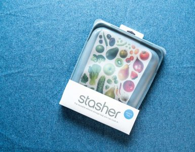 Top view of a stasher bag still in its package, against a blue sheet.
