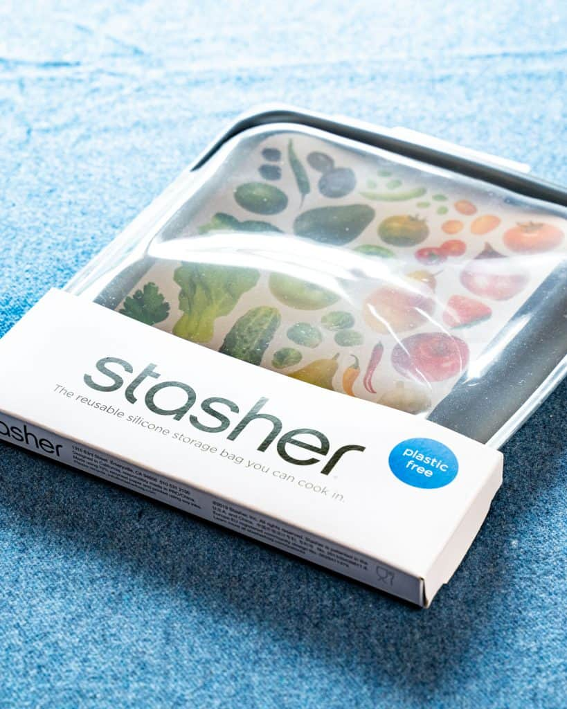 Close-up shot of the Stasher bag, still in its package and placed on a blue sheet.
