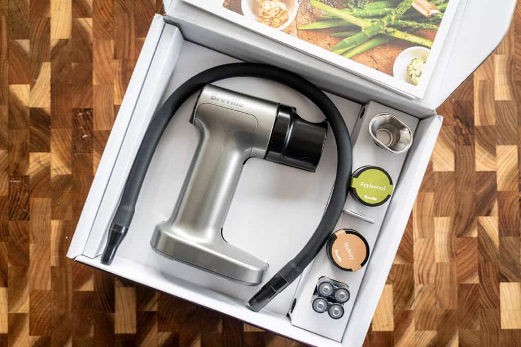 Top view of the box of the Breville smoking gun with the main product plus all of the accessories visible.