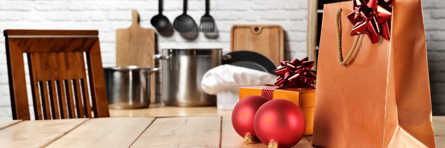 Christmas ornaments and a golden gift bag on a table, with kitchen tools in the background.