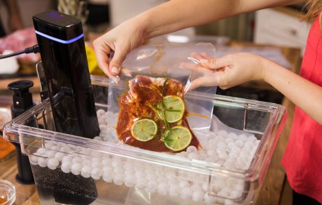 Woman placing vacuum-sealed bag of food into a container full of water and a sous vide machine.