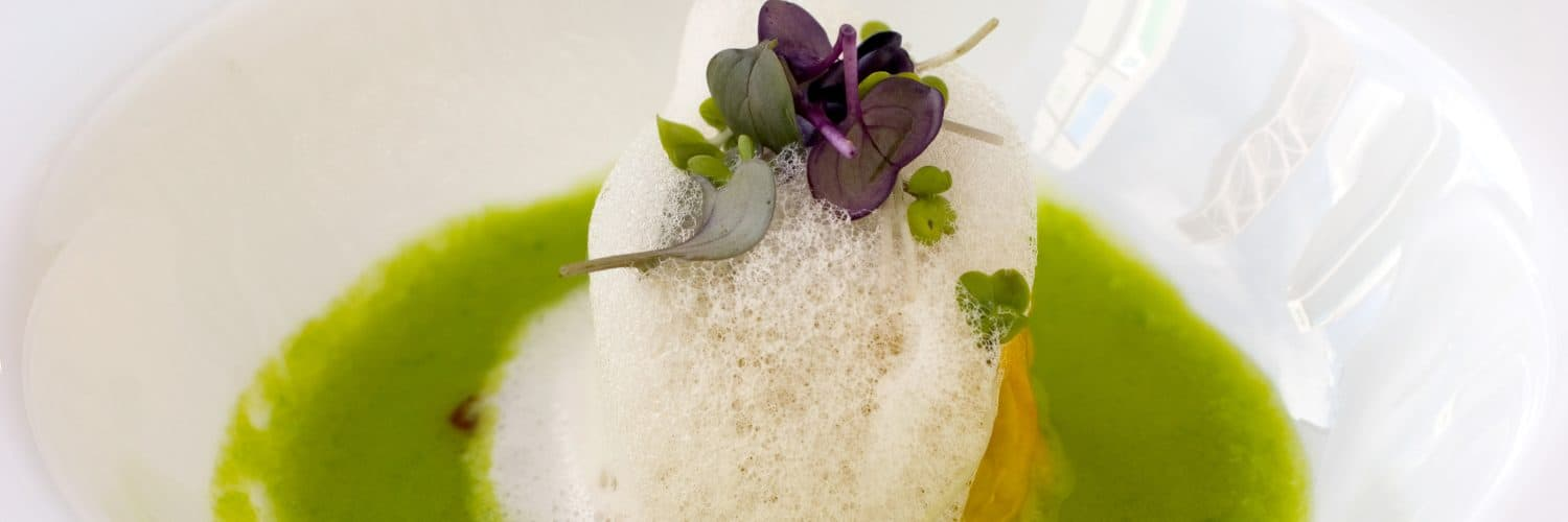 Close-up shot of dish with espuma (or foam) as the main focus, with flower petals and herbs on top and brown liquid on bottom.