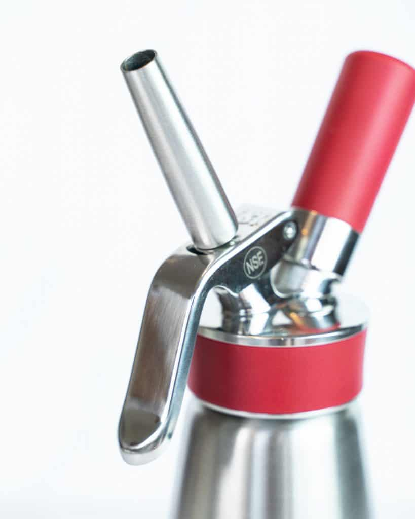 Close-up shot of the top of the Isi Whipped Cream Dispenser with the attachments.