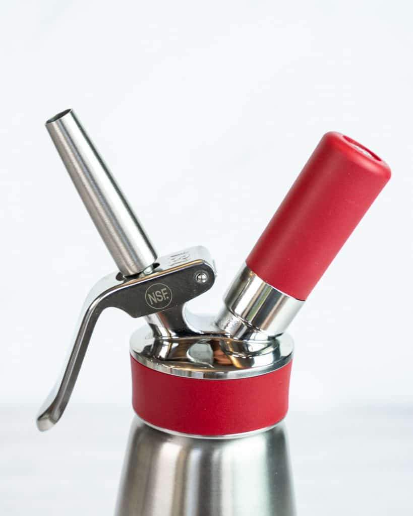 Close-up shot of the top of the Isi Whipped Cream Dispenser showing the charger chamber and a stainless steel attachment.