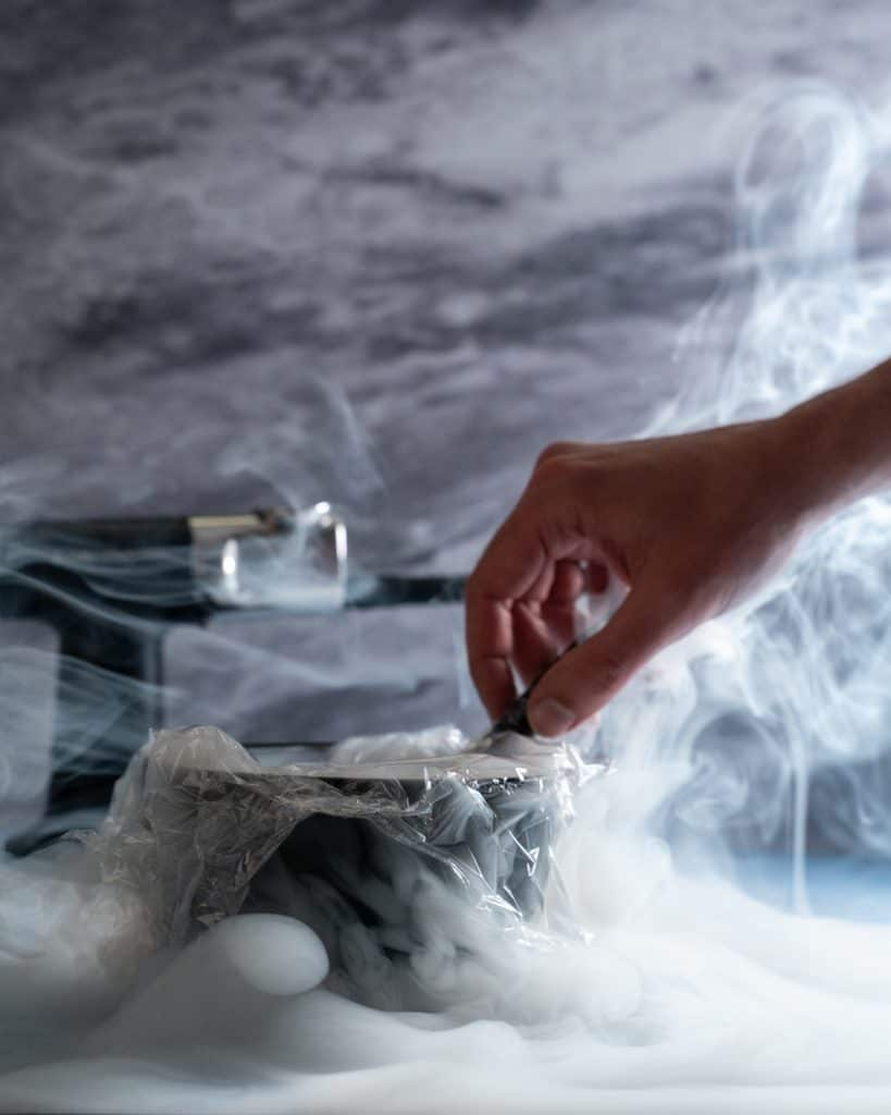 Side view of a bowl with plastic wrap on top and a hand inserting the hose of the PolyScience smoking gun into the bowl, with smoke around it.
