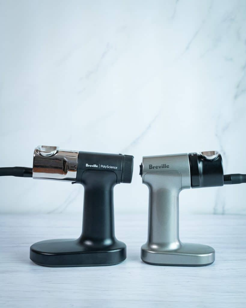 Side view comparison between the PolyScience smoking gun on the left and the Breville smoking gun on the right, showing how the PolyScience is slightly bigger.