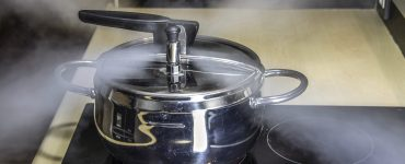 Pressure cooker with steam rapidly coming out of the top of the closed lid