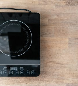 Top view of a single burner induction cooktop on a wooden surface