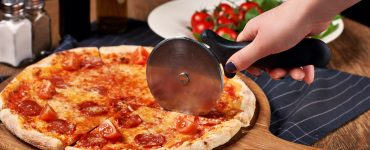 Hand using a pizza wheel to cut a pepperoni pizza placed on a round wooden board